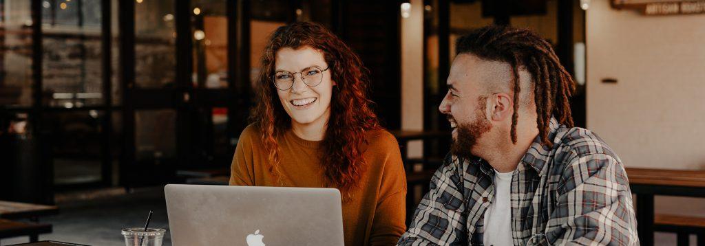 Två glada unga entreprenörer med laptop i coworkingmiljö